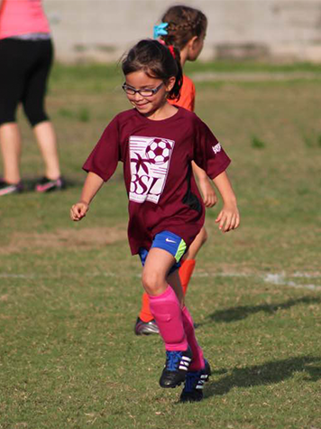 Young Girl Running and Smiling While Playing Soccer